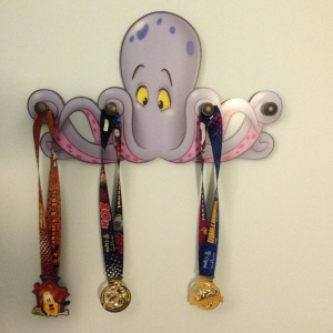 "5k, 10k, and half marathon medals on my ""medal rack"" at the Art of Animation!"